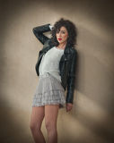 Charming young curly brunette woman in lace short skirt and black leather jacket leaning against a wall. Sexy gorgeous young woman Royalty Free Stock Image