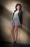 Charming young curly brunette woman in lace short skirt and black leather jacket leaning against a wall. gorgeous young woman. With long legs near wall. Full stock photography
