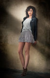 Charming young curly brunette woman in lace short skirt and black leather jacket leaning against a wall. Sexy gorgeous young woman Stock Photos