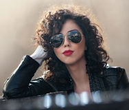 Charming young curly brunette woman with sunglasses and black leather jacket against wall. Sexy gorgeous young woman. With modern look. Portrait of sensual girl Stock Photos