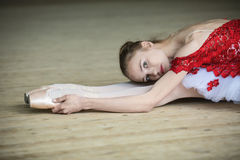 Charming young dancer doing stretching leaned over, looking at t Royalty Free Stock Photos