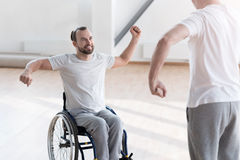 Charming young disabled patient training in the gym. Physical therapy with my coach . Diligent cheerful smiling disabled men repeating exercises after the Royalty Free Stock Images