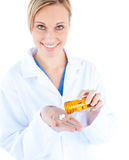 Charming young doctor holding pills Royalty Free Stock Photography