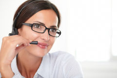 Charming young employee conversing on headphones. Charming young employee with spectacles conversing on headphones while smiling Royalty Free Stock Photography