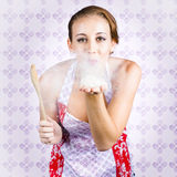 Charming young female cook blowing baking kiss Stock Image