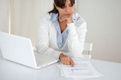 Charming young female studying documents at office Stock Photo