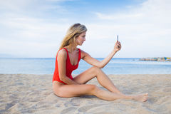 Charming young female in swimwear taking self portrait with smart phone Stock Image