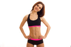 A charming young fitness girl with elastic tummy looks into the camera keeps your hands on the sides and smiling Royalty Free Stock Image