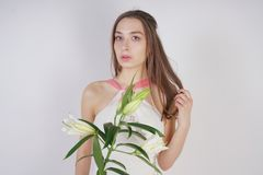 A charming young girl with big eyes and brown hair stands without makeup in a fashion dress on a white background in the Studio. b. Eautiful young teen woman royalty free stock images
