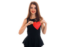 A charming young girl in black dress holding a red heart and smiling Royalty Free Stock Photo