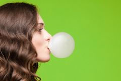 Side view of beautiful girl blows a sphere from chewing gum. Charming young girl blowing bubble from chewing gum royalty free stock photos