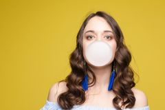 Side view of beautiful girl blows a sphere from chewing gum. Charming young girl blowing bubble from chewing gum royalty free stock photography