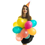 Charming young girl with a cone on her head smiling looks straight and keeps a lot of hot air balloon Stock Photos