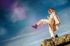 Freedom feeling over sky. A charming young girl with curly fair hair in fashionable clothes. Fashion, beauty stock image