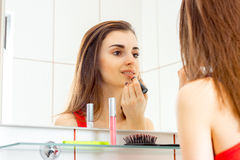 A charming young girl does makeup in front of a mirror. At the bathroom stock images