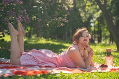 A charming young girl enjoys a rest and a picnic on the green summer grass alone. pretty woman have a holiday. A charming pin up vintage retro young girl enjoys royalty free stock images