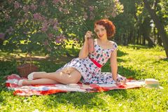 A charming young girl enjoys a rest and a picnic on the green summer grass alone. pretty woman have a holiday. A charming pin up vintage retro young girl enjoys stock images