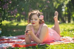 A charming young girl enjoys a rest and a picnic on the green summer grass alone. pretty woman have a holiday. A charming pin up vintage retro young girl enjoys stock photo