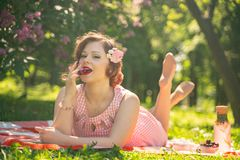 A charming young girl enjoys a rest and a picnic on the green summer grass alone. pretty woman have a holiday. A charming pin up vintage retro young girl enjoys royalty free stock photo