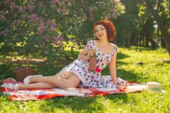 A charming young girl enjoys a rest and a picnic on the green summer grass alone. pretty woman have a holiday. A charming pin up vintage retro young girl enjoys royalty free stock photos