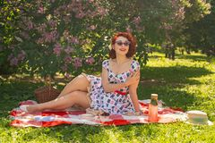 A charming young girl enjoys a rest and a picnic on the green summer grass alone. pretty woman have a holiday. A charming pin up vintage retro young girl enjoys royalty free stock image