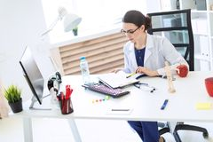 A beautiful young girl in a white robe is sitting at a computer desk with documents and a pen in her hands. A charming young girl with glasses, a blue blouse Royalty Free Stock Photography