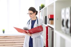 A beautiful young girl in a white robe is standing near the shelter and flips through a red folder with documents. A charming young girl with glasses, a blue Royalty Free Stock Image