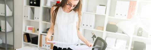 A young girl in the office is standing near the table and looking at documents. A charming young girl with glasses, a white blouse and black pants is standing royalty free stock photo