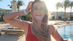 Portrait of charming young girl with golden hair blowing in wind, in red sexy bikini, turns to camera and smiles. Pool stock footage