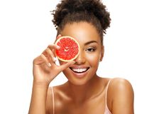 Charming young girl holding a slice of pomelo in front of her face. royalty free stock photography