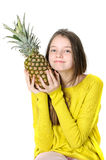 Charming young girl holds a large ripe pineapple in her hands. Stock Photography