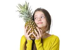 Charming young girl hugs a large ripe pineapple. Royalty Free Stock Photo