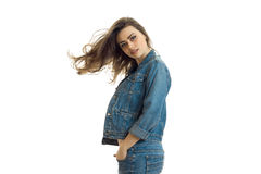 Charming young girl in jeans jacket looks straight and her hair fly through the air. Isolated on white background stock photos