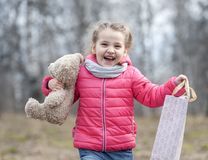 The charming young girl joyfully holds in her hands a packaged box with a gift. Baby holding a teddy bear in hand on the background of wild nature in spring Stock Images