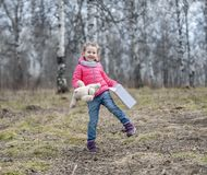 The charming young girl joyfully holds in her hands a packaged box with a gift. Baby holding a teddy bear in hand on the background of wild nature in spring Royalty Free Stock Photos