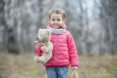 The charming young girl joyfully holds in her hands a packaged box with a gift. Baby holding a teddy bear in hand on the background of wild nature in spring Stock Photography