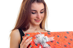 A charming young girl with long hair holds in her hand a great gift wrapping and smiling Royalty Free Stock Photo
