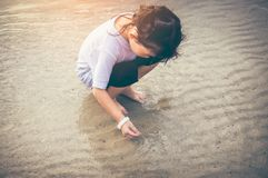 Charming young girl is looking for sea animals on the beach. Asian child playing with sand. Charming young girl is looking for sea animals on the beach. Outdoor Royalty Free Stock Photos