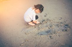 Charming young girl is looking for sea animals on the beach. Asian child playing with sand. Charming young girl is looking for sea animals on the beach. Outdoor Stock Photography