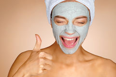Charming young girl with mask of clay on her face. Photo of crazy girl shows thumbs up and smiling. Beauty & Skin care concept Stock Photos