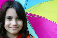 Charming young girl with multicolored umbrella royalty free stock photography