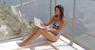 Happy girl with laptop on vacation. Charming young girl in swimsuit chilling on balcony of tropical hotel on coastline of ocean and using laptop while sunbathing stock video footage