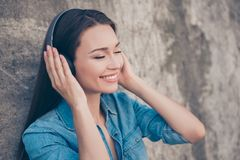Charming young girl with toothy smile is so dreamy and happy, listening to her favourite song, holding the earphones, with closed. Eyes on concrete`s wall Stock Photo