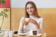 Charming young girl warms up in cafe drinking hot tea, holds cup in hands, going to eat tasty cake, wears smart white dress. stock photography