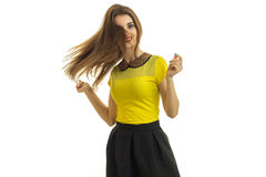 Charming young girl in the yellow shirt is spinning and her hair fly Stock Image