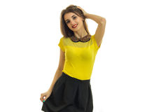 A charming young girl in a yellow t-shirt and skirt smiles and holds her hand near hair Royalty Free Stock Images