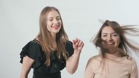 Charming young girls are dancing and rejoices at white background stock video