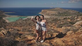 Charming young girls friends take a selfie and shoot on a smartphone to create new content for social networks. Travel