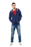 Charming young guy in blue sweatshirt with hands in pockets looking at camera. Stock Photography