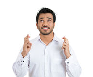 Charming young guy wishing and praying keeping his Royalty Free Stock Photos